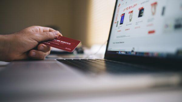 Smartphone und Kreditkarten vor einem Laptop mit Einkaufssymbol